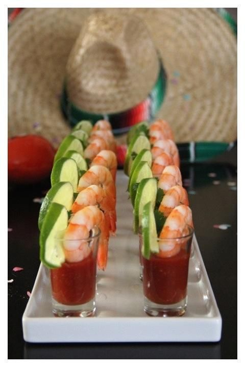 Serve shrimp cocktail in shot glasses, and decorate with lime and a sprig of cilantro