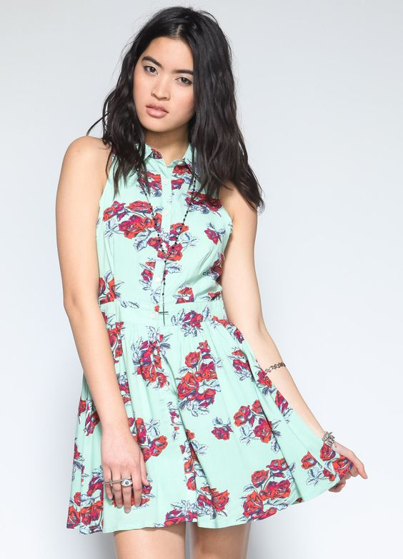Sleeveless shirt dress featuring red and blue floral details, side pockets, and button down closure.