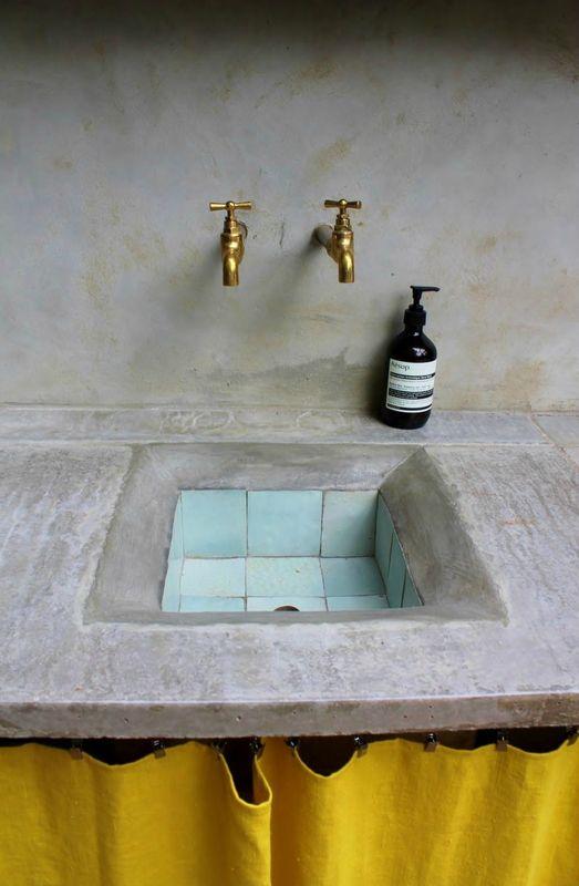 Lavabo creusé  dans un plan pierre/ béton et petits carreaux bleus en faïence.
