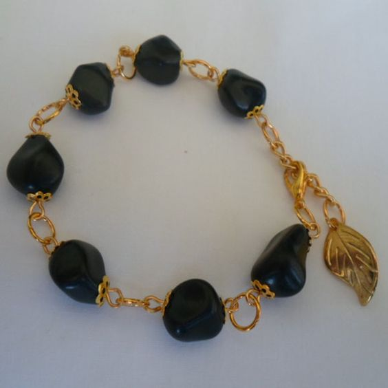 Pulseira feita com pedra reconstituída preta e metal dourado. R$ 4,50