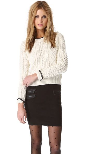 Crop pullover with ribbed hem.  Neck & cuff have faux leather binding.
