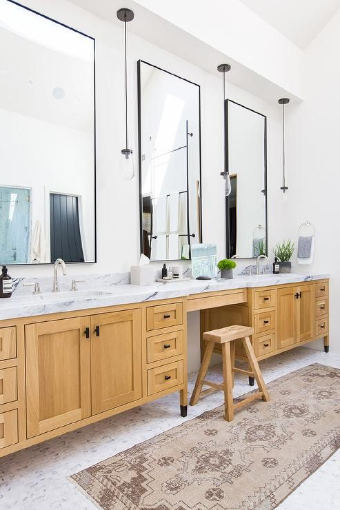 Three Black Framed Vanity Mirrors Lit By Hanging Clear Glass Lights Fixed Over A Blond Oak Washstand Ac White Countertops Oak Bathroom Cabinets Bathroom Vanity