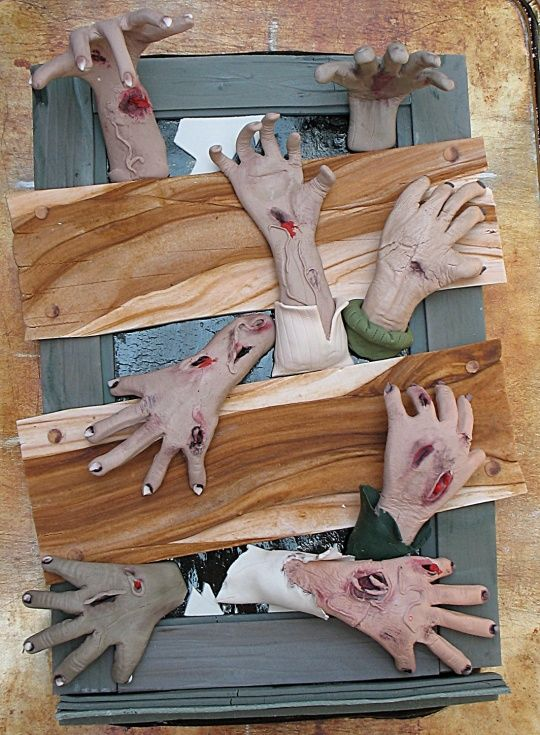 make your house look zombie infested. This is a cake, but you could do this with your home, use cardboard for the wood planks, black Out the windows (tint film) and Halloween hands ( paint Gore on them)