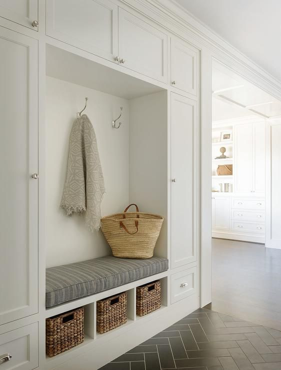 Beautiful white and gray mudroom with gray herringbone tile floors boasts built in white shaker cabinets and closed lockers with round silver pulls framing a mudroom bench finished with a striped gray linen seat cushion and siting atop three cubbies holding brown wicker baskets as polished nickle coat hooks are mounted above the seat.: