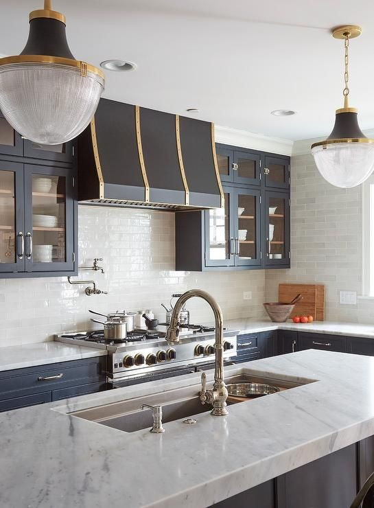 Matte black, gold, and white glass pendants hang above a dark gray island fitted with a thick white quartz countertop completed with a stainless steel trough sink and a polished nickel gooseneck faucet.