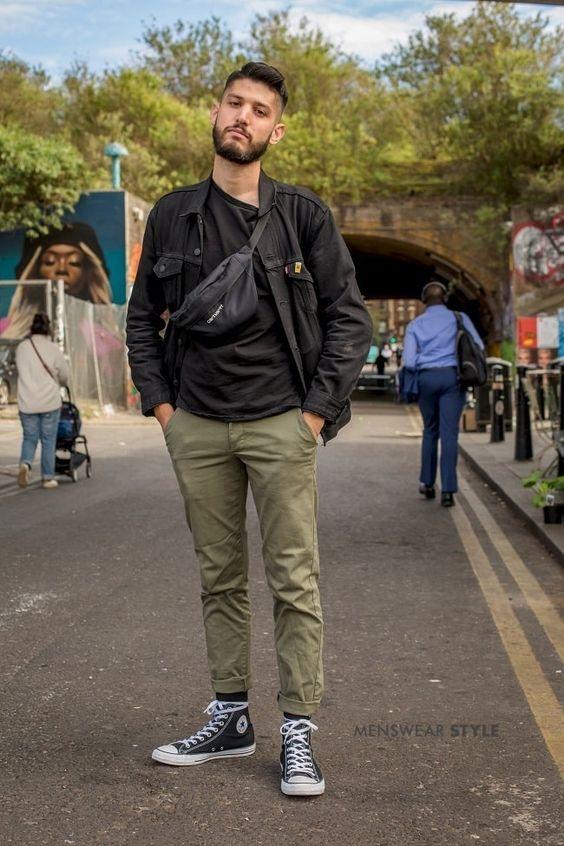 海外メンズブラックデニムジャケットコーデA Street Style Picture of Gianmarco on the streets of London in 2019 wearing Black Converse High Tops, Green Chinos, Black Denim Jacket, and Carhartt Shoulder Bag.