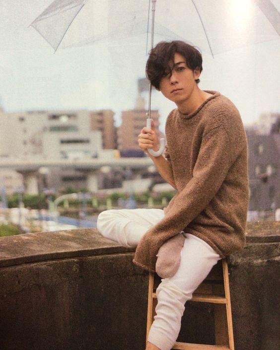 袖の長い茶色のニットを着て傘をさしている高橋一生の画像