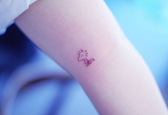 Minimalist Woodstock tattoo on the left inner arm.