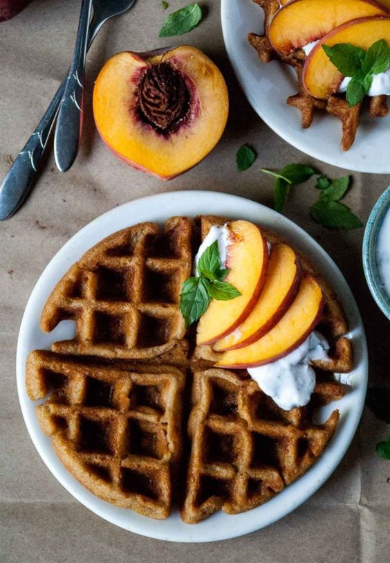 Perfectly crispy vegan and gluten free peach waffles, topped with vegan mint coconut whipped cream and fresh peaches! // @HeartofaBaker