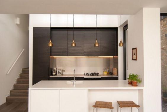 weiße Kücheninsel und Einbauküche mit dunklen Fronten