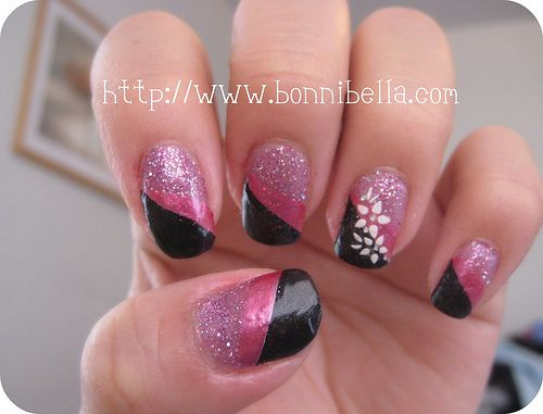 A striped black and pink nail art. Flower on fourth finger (Whats in style is a different design or color on fourth finger).