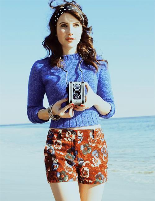 Comprar ropa de este look:  https://lookastic.es/moda-mujer/looks/jersey-con-cuello-barco-azul-pantalones-cortos-de-flores-rojos-cinta-para-la-cabeza-a-lunares-negra-y-blanca/388  — Jersey con Cuello Barco Azul  — Pantalones Cortos de Flores Rojos  — Cinta para la Cabeza a Lunares Negra y Blanca