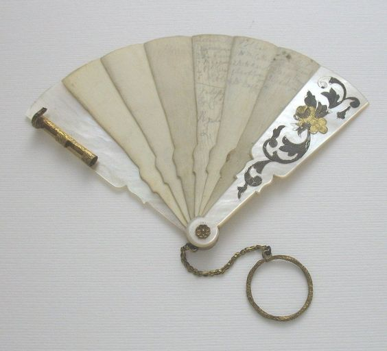 French, Napoleon III era 'carnet de bal' or dance card, in the form of a fan, with MOP covers, 6 Ivory pages or leaves, & a Gilt chain & finger (or chatelaine) ring & dating to around 1850.  The front & rear covers are made from Mother of Pearl, & feature chamfered edges, with the front cover having a thin, twin tone Gold leaf floral & foliate inlay.: