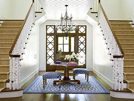 Love the split staircase with its turned spindles, architectural details of the doorway, the chandelier and ceiling. The blue and white rug and benches are beautiful, although I would try placing the benches a little differently.