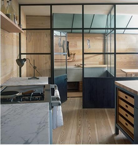 """British bespoke kitchen designers Plain English were inspired by """"the wild beauty of Osea Island"""" in their design for the Osea Kitchen, on view at the company's Marylebone showroom. Steel window framing, cararra marble bench top. Industrial/country aesthetic"""