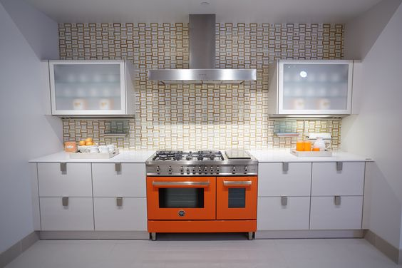 kitchen vignette featuring a bertazzoni stove in orange and swank in