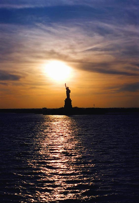 A silhouette view of the Statue of Liberty at sunset with the sun positioned over the torch