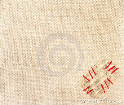 Patch with red stitchs over burlap. Sackcloth