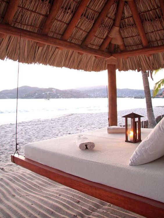 A teak daybed dangles from a grass-topped pavilion overlooking Mexico's Zihuatanejo Bay.