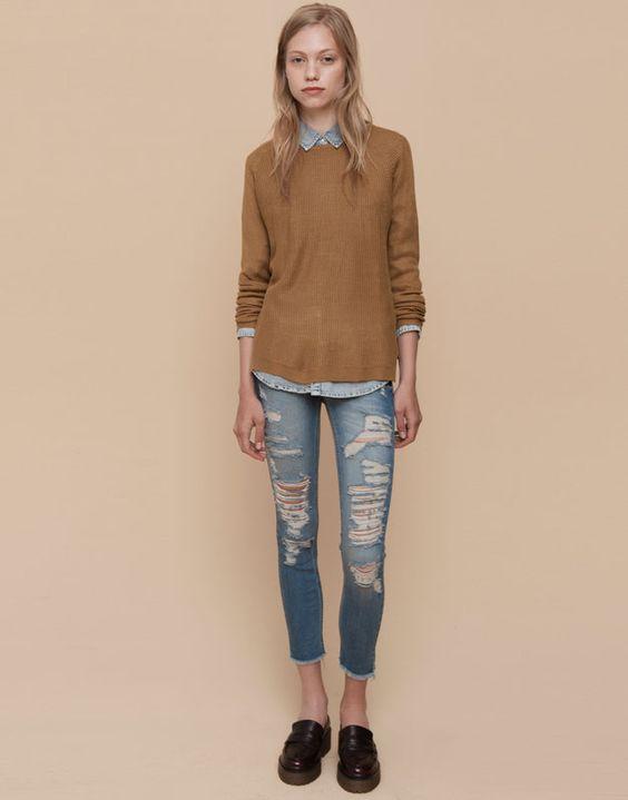 Look de vaqueros rotos, blusa denim y sweater en color camel.