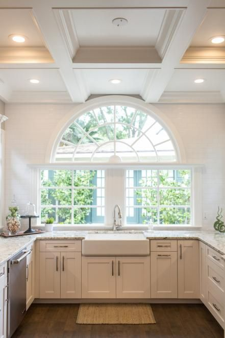A beautiful half circle window is a worthy centerpiece in this sophisticated kitchen with a warm, updated farmhouse feel. A farmhouse sink, subway tile surrounding the window and coffered ceiling all work in stunning symmetry creating a stylish and comfortable feeling of history.