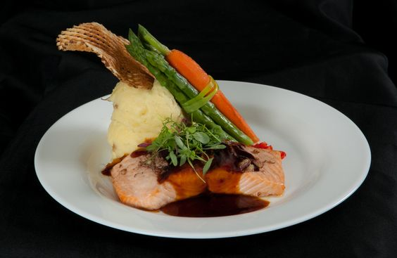 Salmon Teriyaki - Topped with a sesame-studded teriyaki sauce and ginger infused black plum puree — at Warrington Country Club.