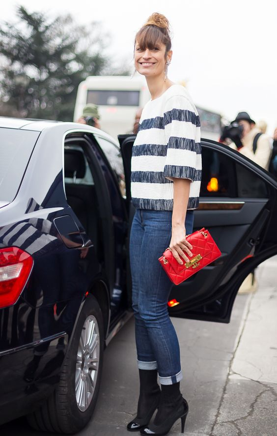 Caroline de Maigret in a striped knit sweater, cuffed jeans, black ankle boots and bold red purse: