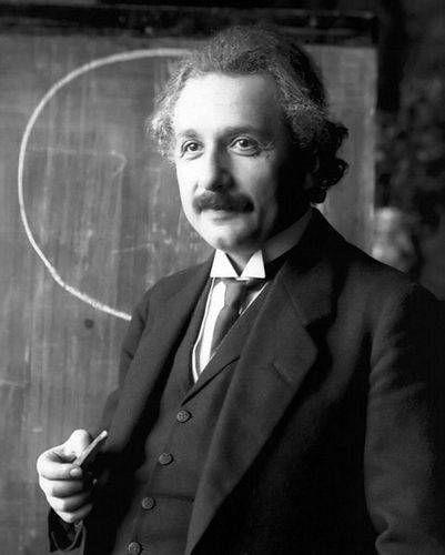 黒板の前に立って微笑んでいるアルベルト・アインシュタインの壁紙・画像