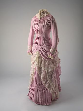 Two piece pink full length wool dress (bodice and skirt) with cream lace trimming. Both cuffs and collar are trimmed with cream lace. Round copper buttons run down the centre-front and feature an anchor design. The skirt is pleated and layered with extra fabric and trimmed with cream lace.   This fine wool dress dates from about 1885 and belonged to one of the daughters of pastoralist, William Pitt Faithfull, founder of the pioneering merino stud, Springfield.
