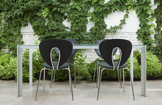 Patio del estudio fotografiado por la Firma Stua con mesa Deneb y sillas Globus en negro
