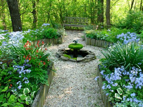 A garden with peastone path, small fountain and spring flowers in bloom