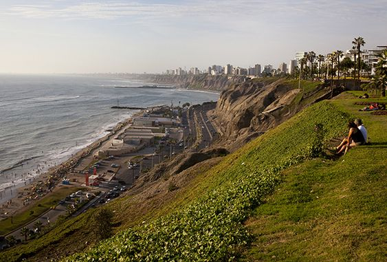 Two people sitting on the hill on the malecon in Lima