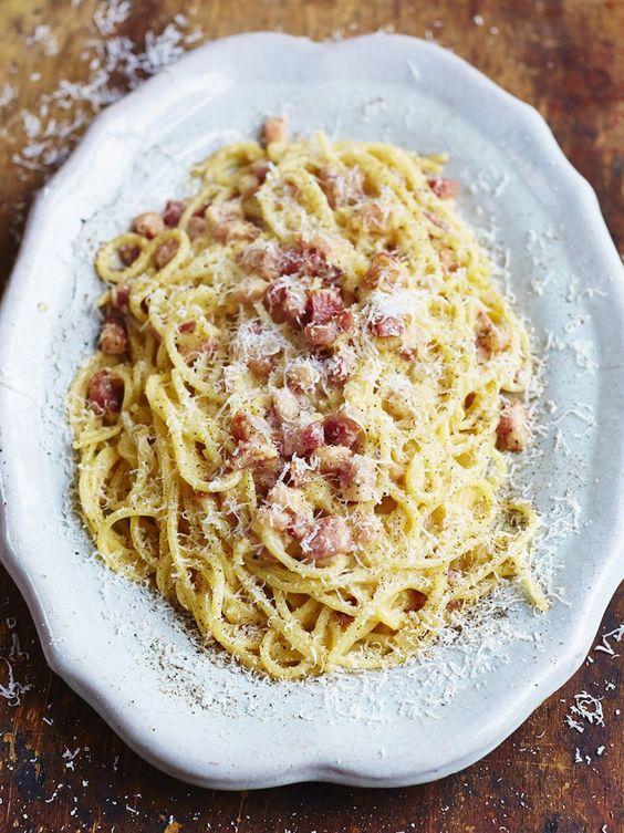 Gennaro's classic spaghetti carbonara : 3largefree-range egg yolks  40gParmesan cheese, plus extra to serve  sea salt  freshly ground black pepper  1 x 150gpiece of higher-welfare pancetta  200gspaghetti  1clove ofgarlic, peeled  extra virgin olive oil