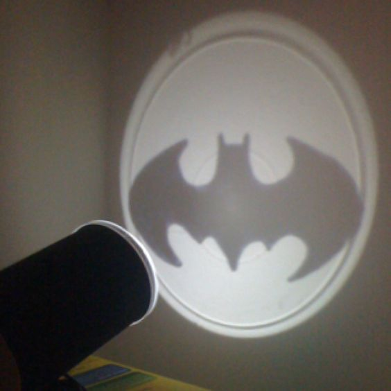 Homemade batlight from a pringles can and a booklight. Using sharpie to color the logos on the caps we made a old batman logo, the dark knight logo, and a superman one