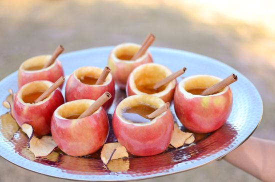 warm apple cider in hollowed out apples with a cinnamon stick