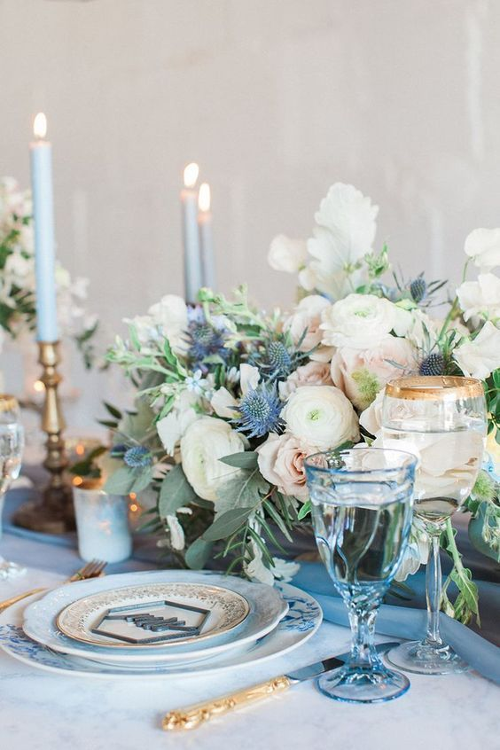 A Gorgeous Floral Centerpiece With Creamy And Blush Blooms Plus Blue Thistles Blue Centerpieces Wedding Table Settings Blue Themed Wedding
