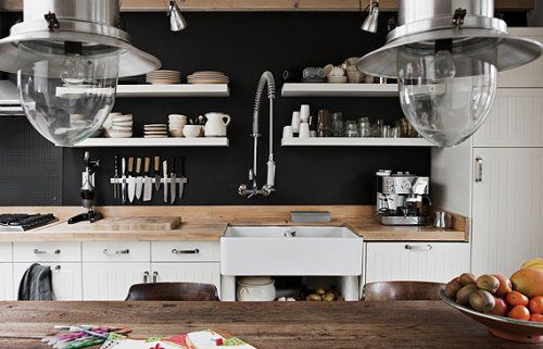 I love how the rustic table contrasts with the super white cabinetry and black painted walls.