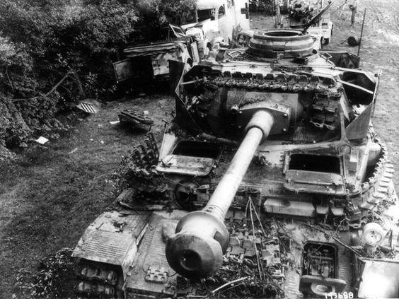 """Un convoi allemand détruit dans un chemin à 8 km à l'ouest de Sées. Au premier plan un Panzer IV et derrière le Panzer un Flak 88, sur ses """"essieux remorques  D'autres épaves de véhicules sur le bas côté droit : une Horch type 40 ou 830R ?, une ambulance, tout au fond derrière l'ambulance une Sdkfz kettenkrad"""