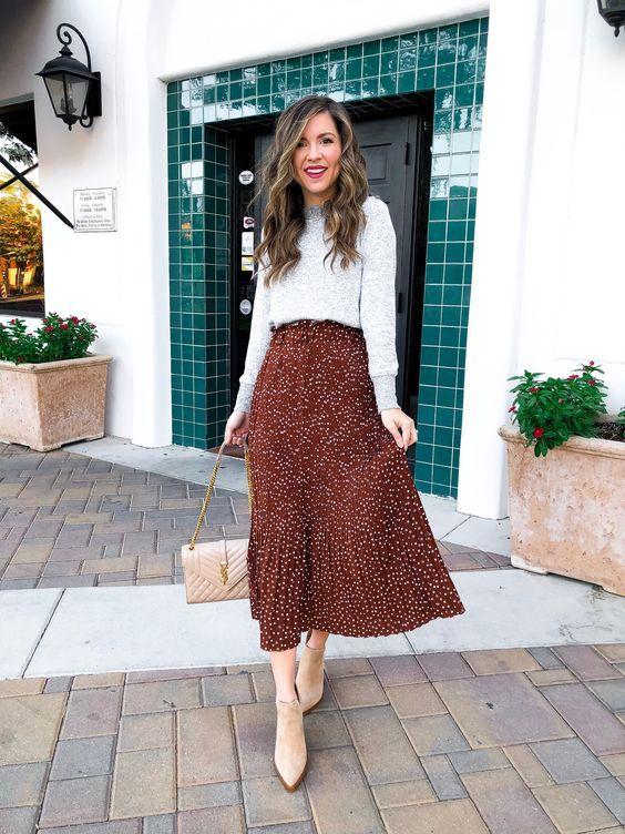 Mujer de estilo chic con falda larga como prenda de vestir, botines y bolso en tono neutro y sueter gris