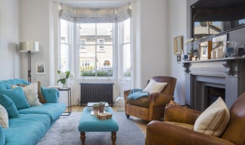 The vivid teal sofa and footstool in the living room of  this Victorian home rich with bold colours and original features, demonstrate a confident use of colour that really brings the space to life.