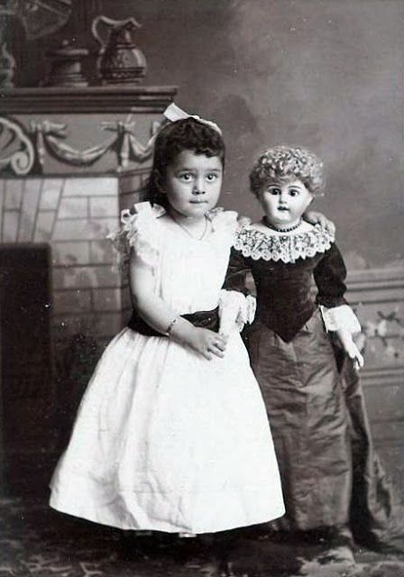 Antique photo of little girl with large doll.
