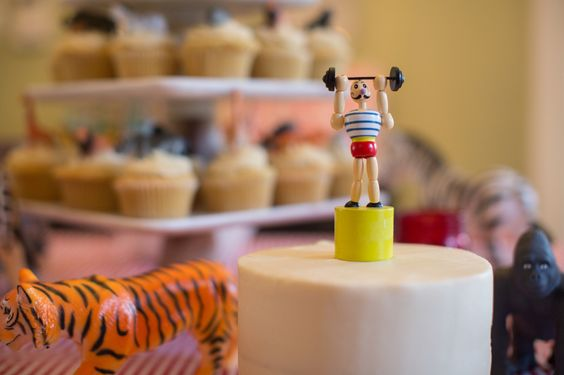 We love the idea of a super simple smash cake with a fun cake topper! Strong man is perfect for a circus party. #socialcircus