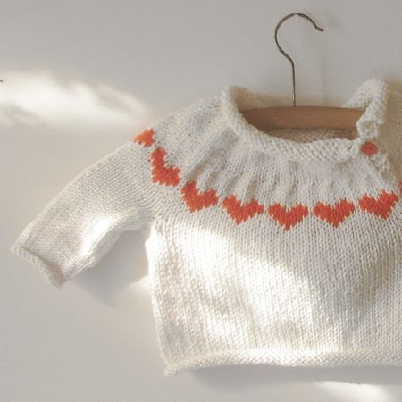 Hand knitted baby sweater with colorwork hearts coordinating with the buttons at neckline.