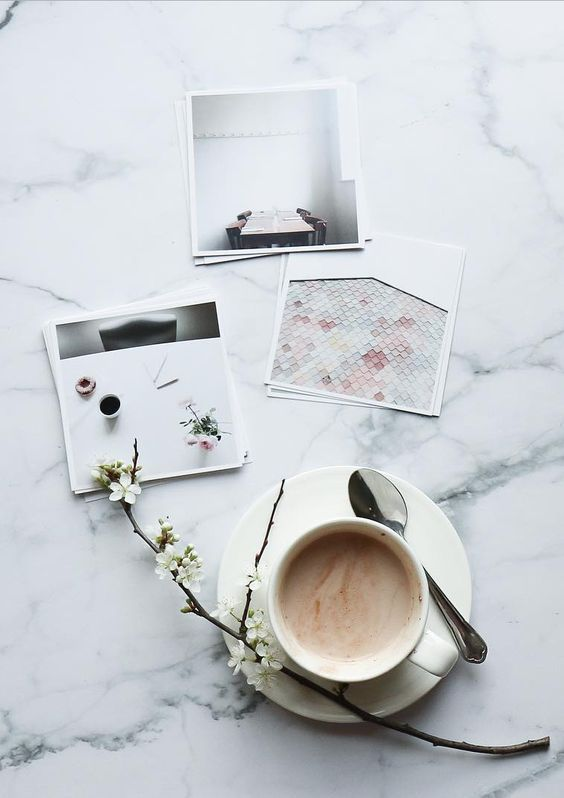 Can't wait for Spring! Love branches in blossom. Coffee  and square prints on a white marble table. Prints from Inkifi.