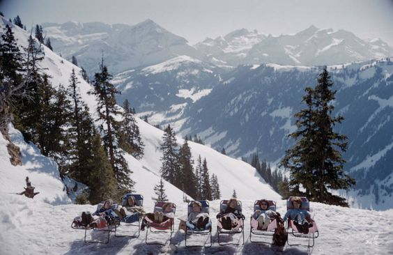 Holidaymakers in sun loungers on the slopes in Gstaad. Photograph by Slim Aarons. #slimaarons #gstaad: