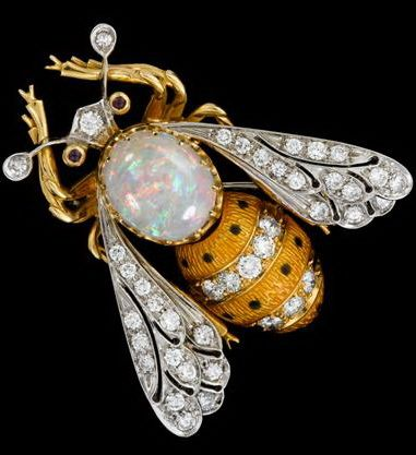 18 karat yellow gold, platinum and diamond 'bee' pin   White oval opal prong set, followed by yellow enameled abdomen accented by petite round cut diamond bands. Detailed platinum, diamond set wings, and diamond set antennae.