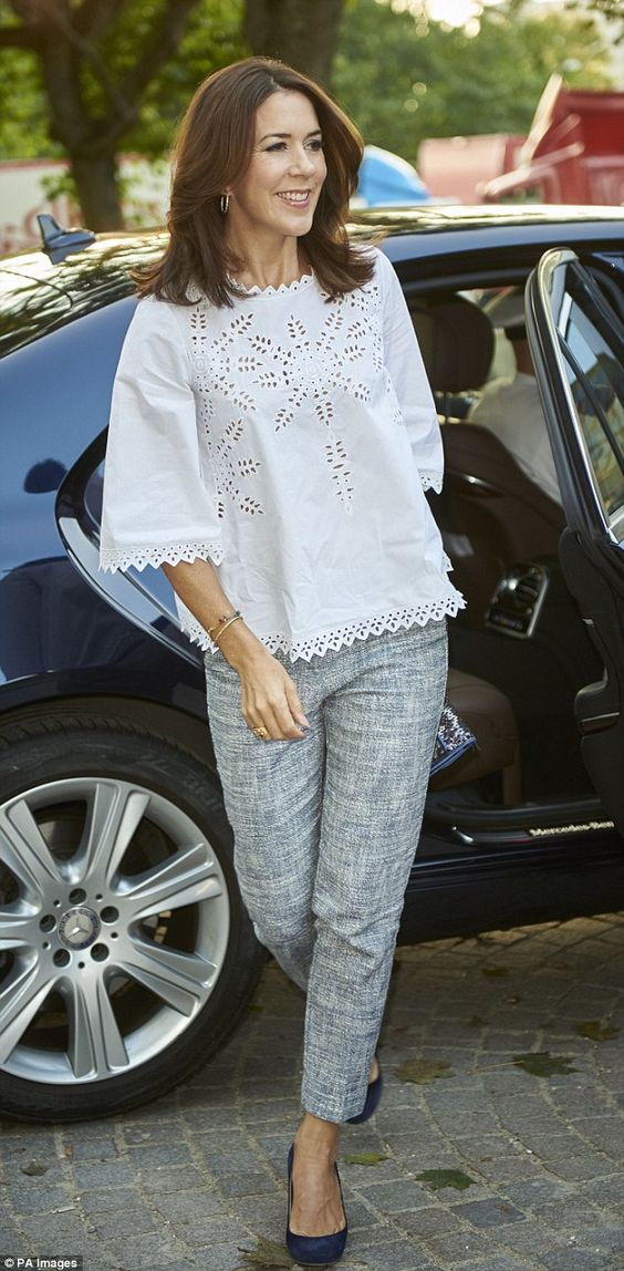 Stylish: Mary wore a cut-out white top, simple grey trousers and navy blue…