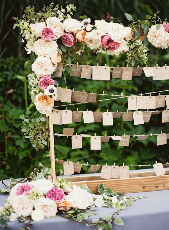 Escort card display table covered in beautiful floral blooms