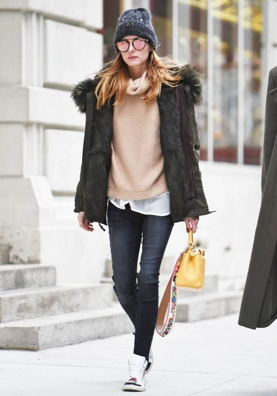 Olivia Palermo wears a cowl-neck sweater, fur-trimmed parka, skinny jeans, high-top sneakers, a Fendi bag, beanie, and mirrored sunglasses: