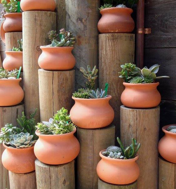 Rock garden with a difference: terracotta pots with succulents on wooden poles.